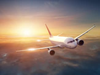 Flugzeug am Himmel vor Sonnenuntergang